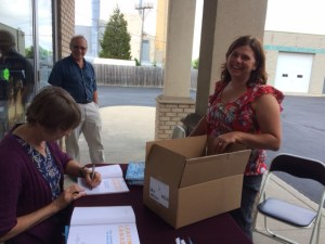 Author Rosabel Fast signs a book for a Wheatley public school teacher at the book launch in Leamington, Ontario.