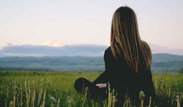 woman wearing black long sleeved shirt sitting on green grass field near mountain under cloudy sky