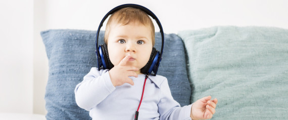 Adorable baby boy listening music at earphones.