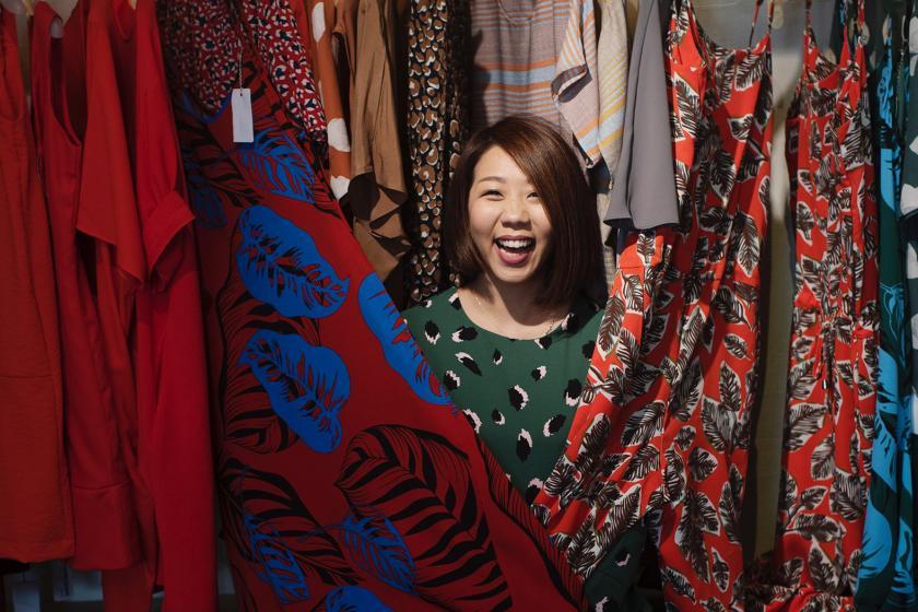 Frau zwischen Kleidern | Plus-Size-Mode | Credits: Unsplash