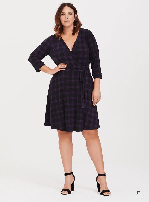 Woman wearing purple and black plaid wrap dress