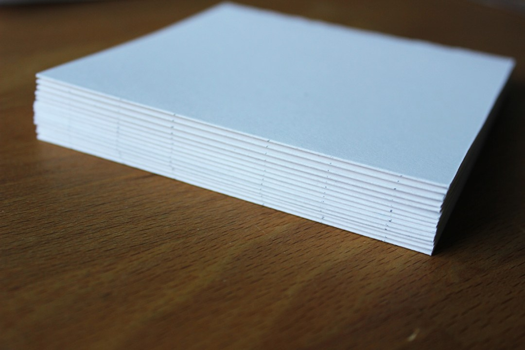 Stack the folded papers and mark the needle openings with pencil