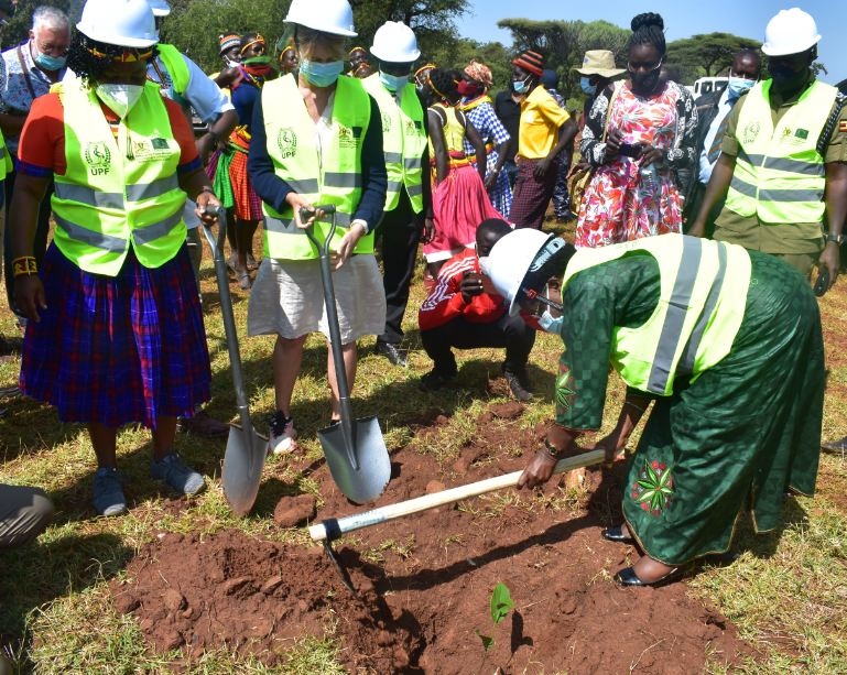 Minister Kitutu plants a tree shortly after the ground breaking ceremony