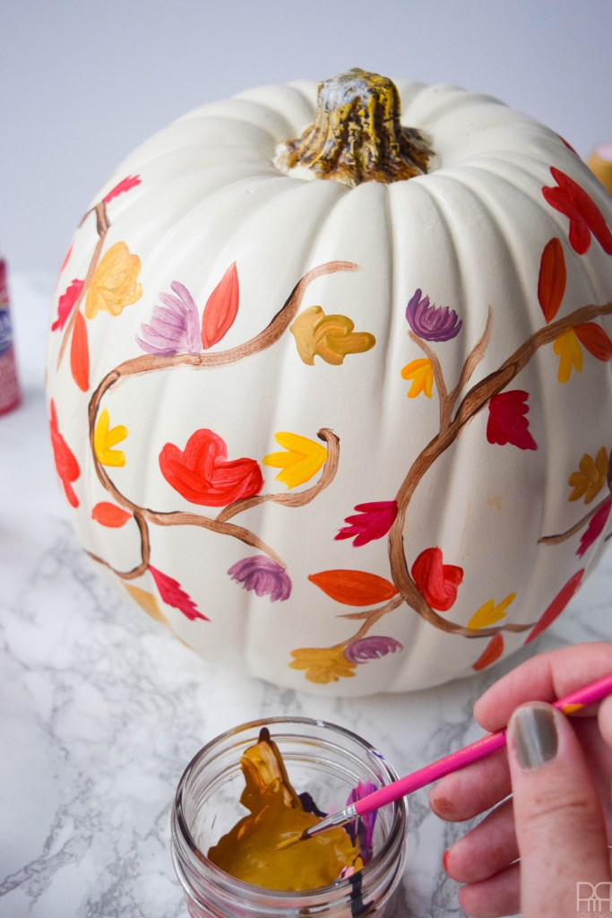 picture of painted white pumpkin with fall leaves