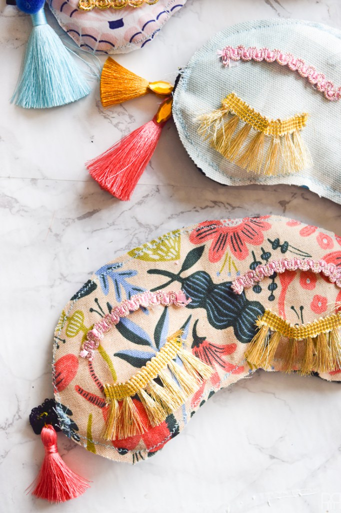 Make your own DIY Holly Golitghtly Sleep Masks with the supplies you may already have. Colourful tassels and pom poms, fringe, and fabric scraps are all you need for these fun sleep masks that would also make a great gift.