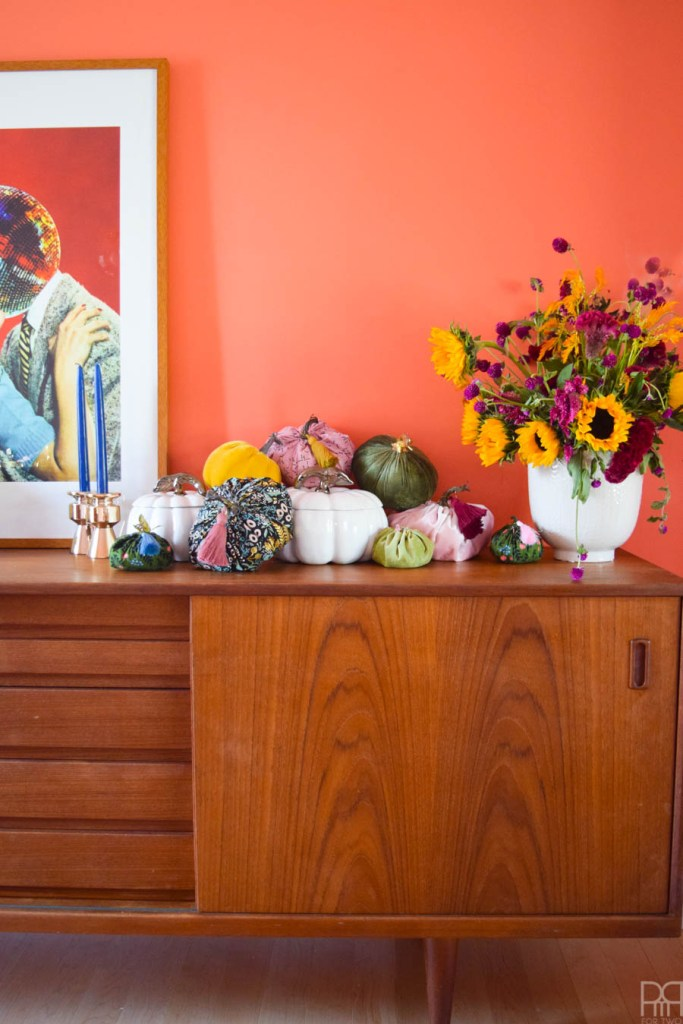 colourful fabric pumpkins with white pumpkin soup tureens, and fall flowers on an MCM sideboard