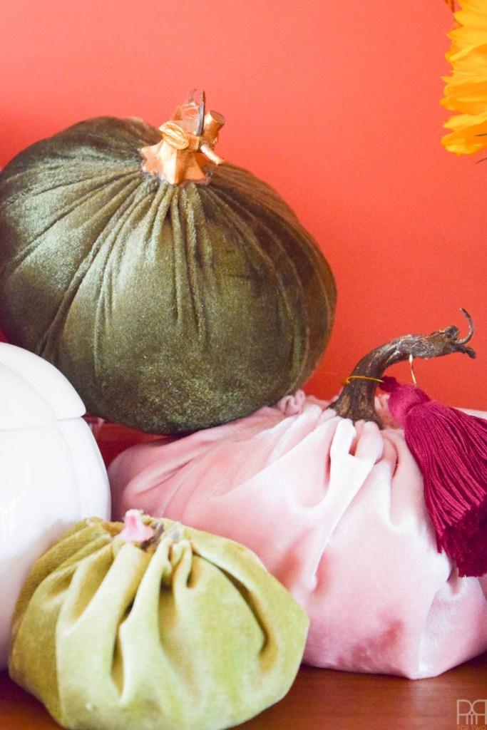 close-up of DIY fabric pumpkins against orange wall