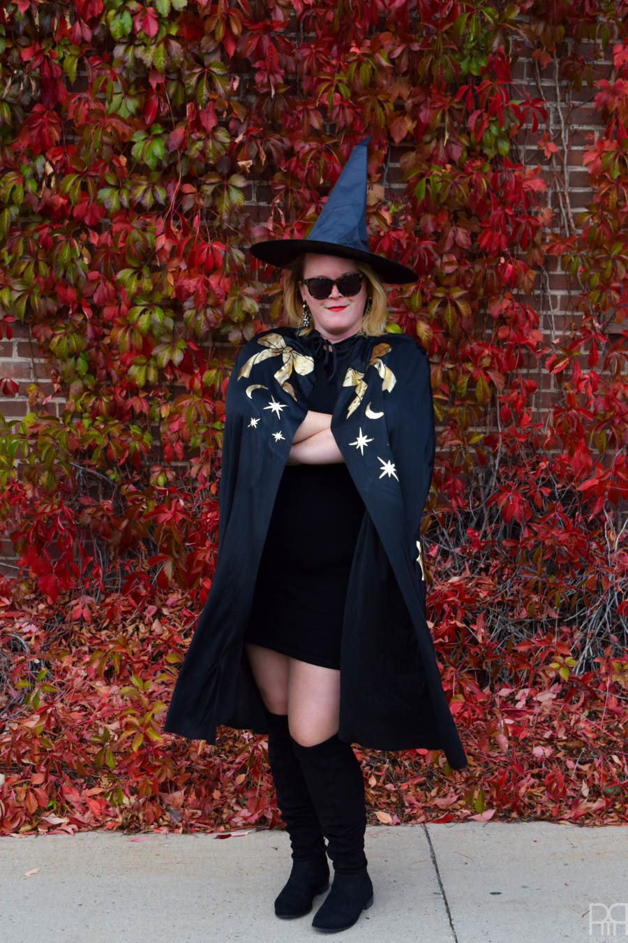 woman with arms crossed, in a witch costume in front of red leaf wall