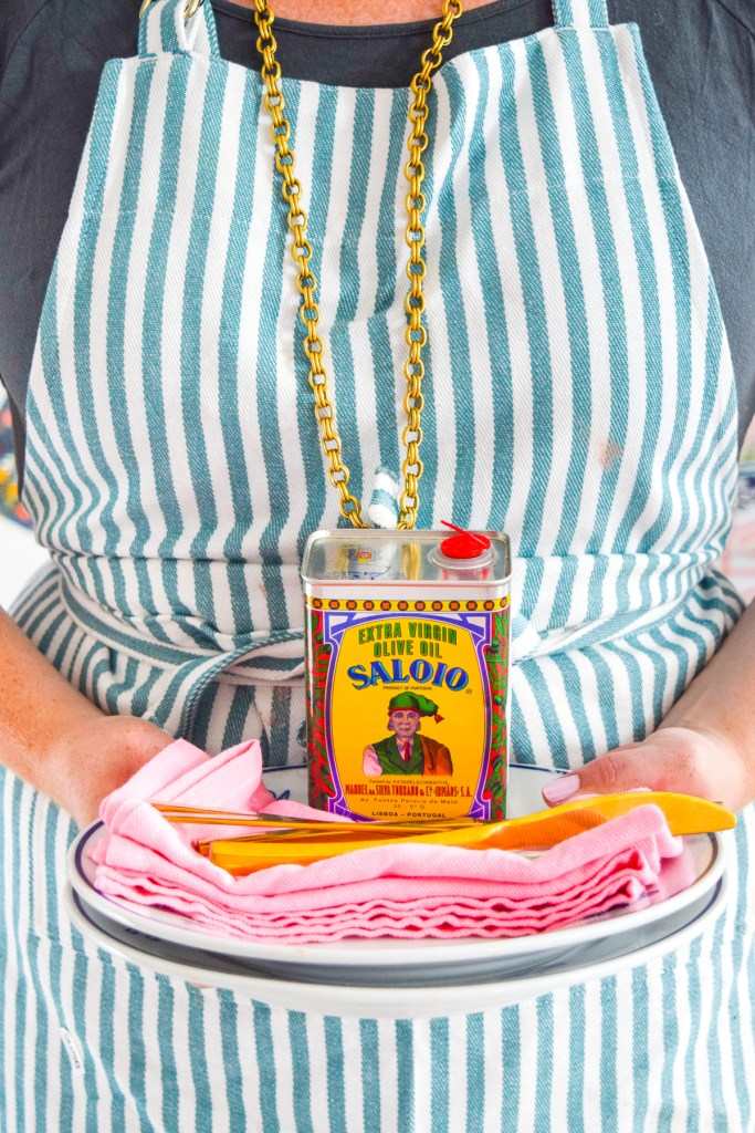 woman in apron holding plates with olive oil