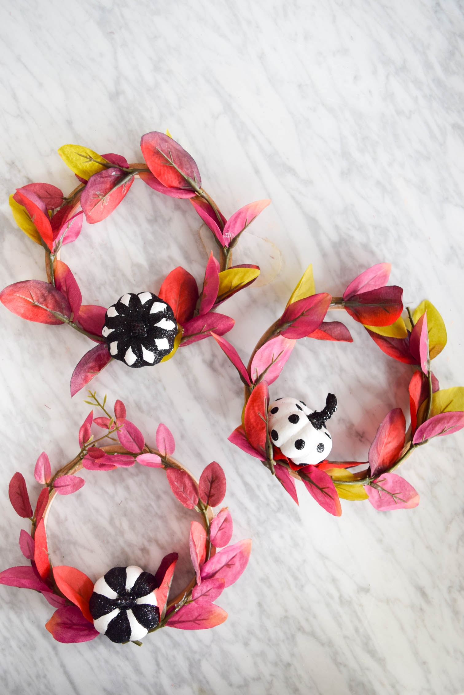 3 mini purple wreaths with pumpkins on a marble table