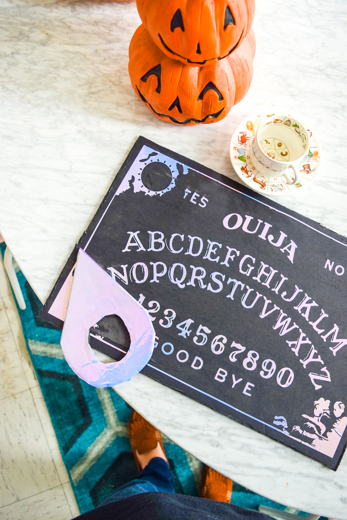holographic ouija board sitting on a marble table with stacked pumpkins