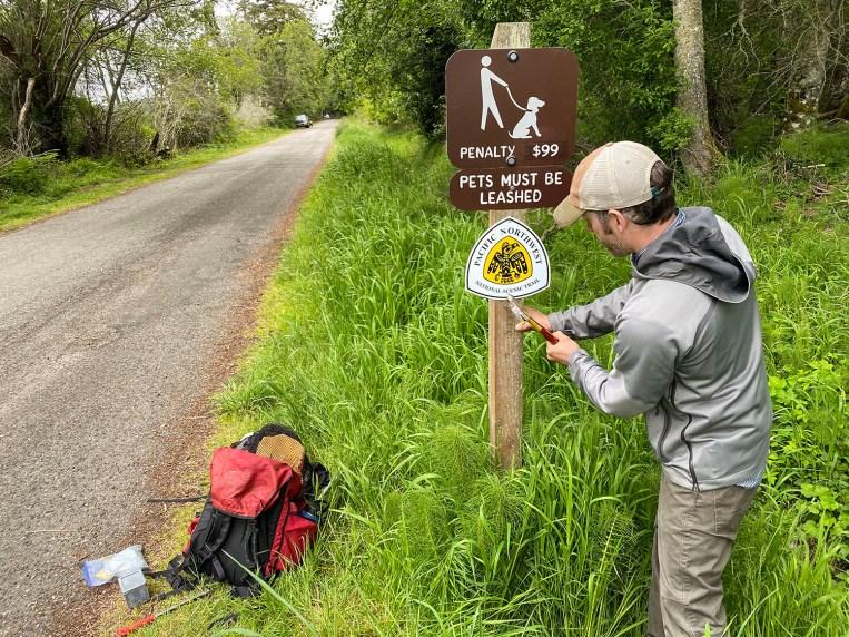 Regional Coordinator Sterling Collins-Hill installs a marker at a trailhead.