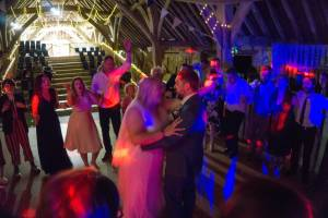The bride and groom dancing together. dancefloor is full with people dancing at The Great Barn in Titchfield. The Pocket Rockers are performing at a Jess and Adam's Wedding.