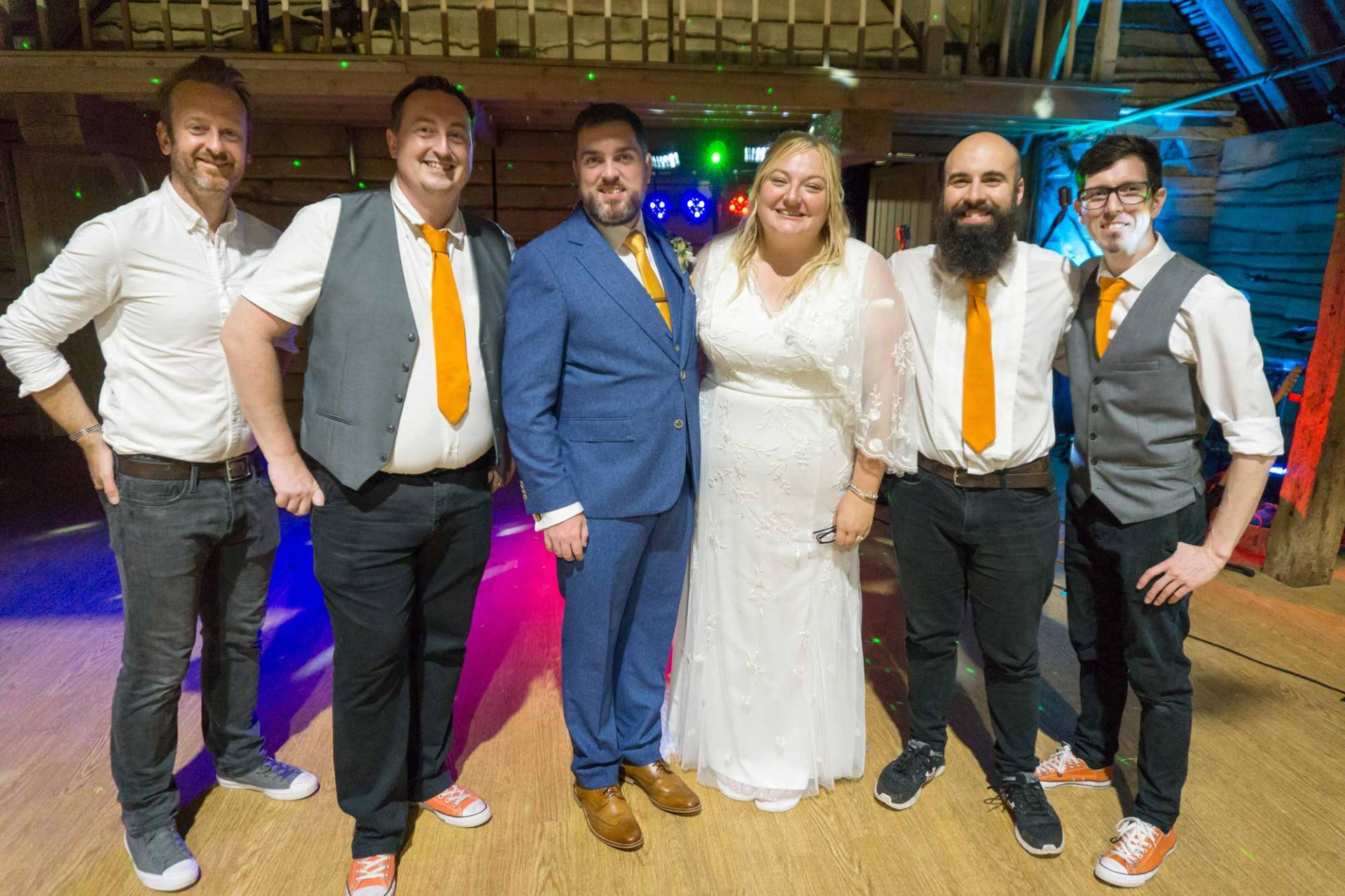The Pocket Rockers pose with the bride and groom at their wedding at The Great Barn in Titchfield