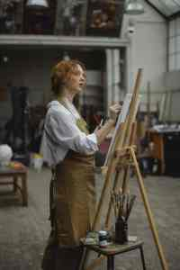 young woman in brown apron sketching on white cardboard