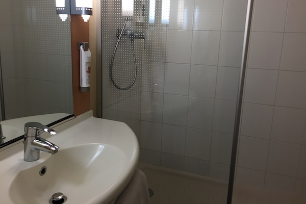 Bathroom sink and shower at Ibis Calais Hotel