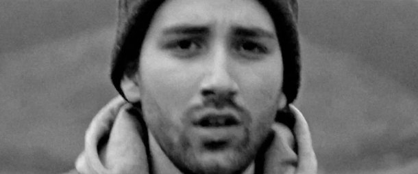 A  black and white close up image of lead singer Tigrane Minassian from Classroom Battles running down a road on a deserted moor taken from the video for the single Crosseyed horse.