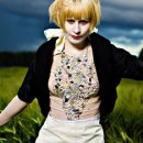 A striking image of Jenny Hval stood in a dark green field with a dark brooding sky behind her. Her make up is gothic and she is wearing a black and cream dress which is beaded elaborately down the bodice. She is lit brightly and appears very stark against the dark background.