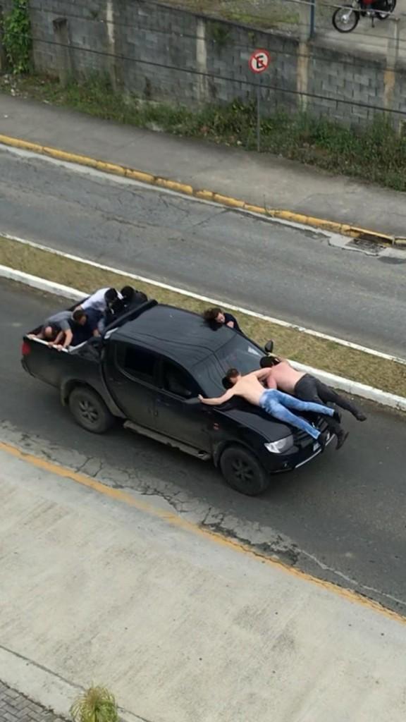 assalto no alto vale - Criminosos fogem da polícia com reféns presos em capô de caminhonete - VEJA VÍDEO