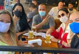 Adriano Imperador se diverte em barzinho com amigos e só bota máscara na hora da foto