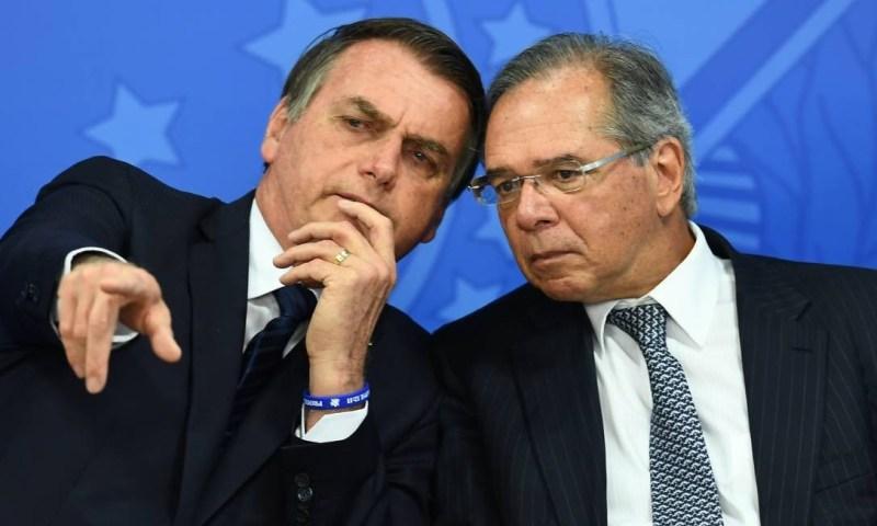 83702528 Brazilian President Jair Bolsonaro L and his Finance Minister Paulo Guedes talk during - Governo planeja campanha em TV e rádio para festejar criação de empregos