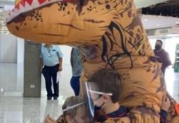 Mãe se fantasia de dinossauro para se proteger da Covid-19 e receber filhos em aeroporto