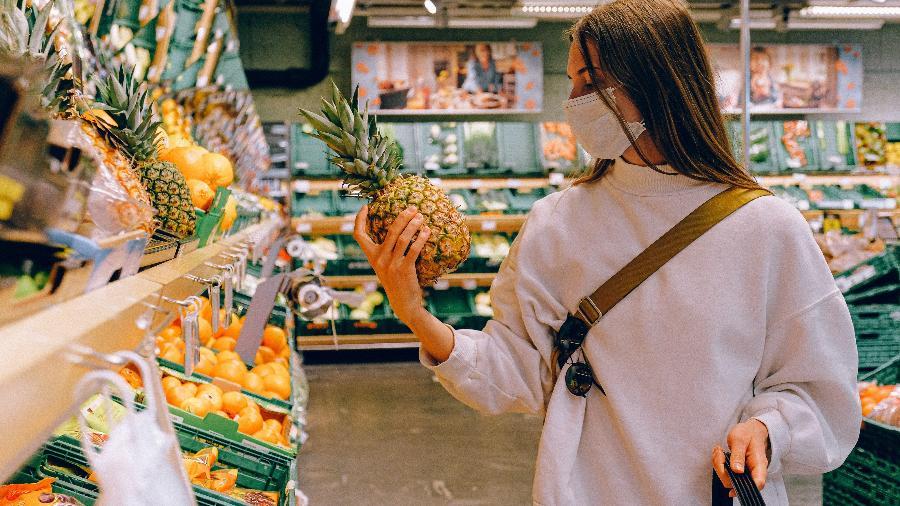 consumidora olha abacaxi em um mercado supermercado compras 1596738549792 v2 900x506 - FDA: Transmissão da Covid-19 por embalagens e alimentos é 'muito improvável'