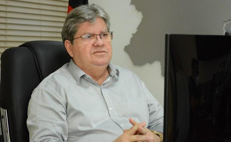 Joao olha para o computador - João Azevêdo assina ordem de serviço para conclusão de adutora e anuncia licitações de estradas