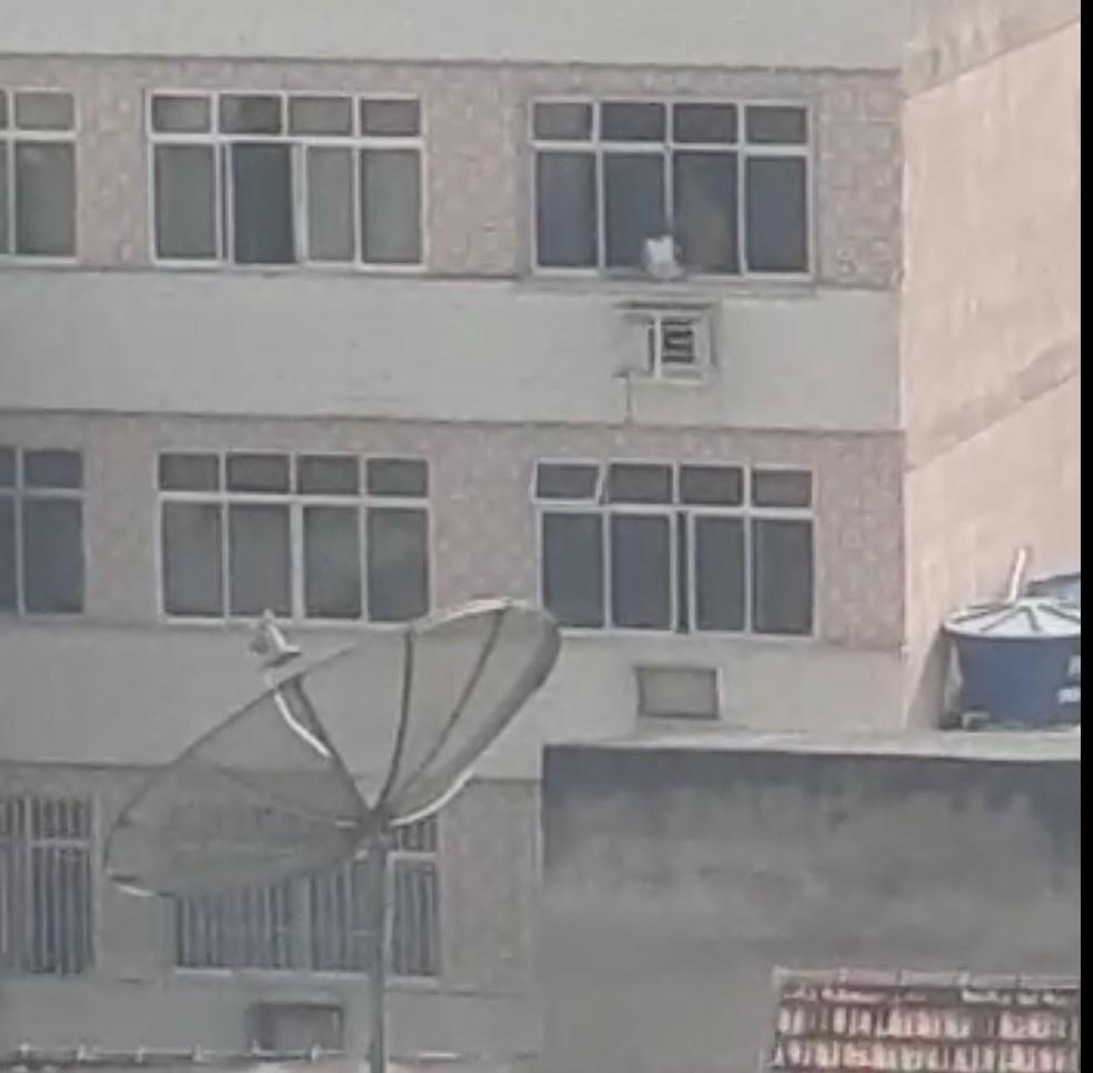 janela - Homem é visto colocando uma criança para fora da janela do prédio e alega que foi apenas uma 'brincadeira'