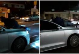 PERIGO! Homem é flagrado no capô de carro em movimento em avenida