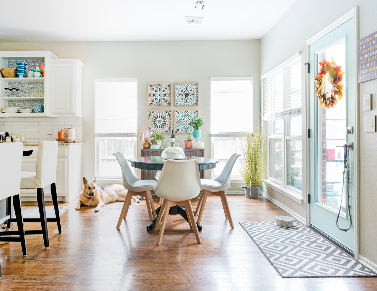 Eat in kitchen nook with aqua door, pops of orange and white modern chairs from Amazon.