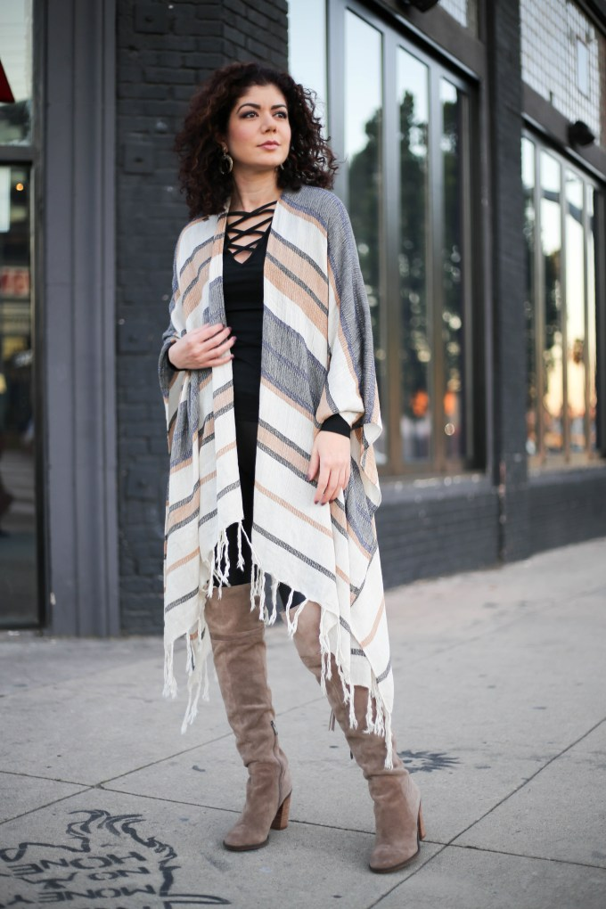 Polished whimsy in leather leggings, criss cross top, over the knee boots and poncho