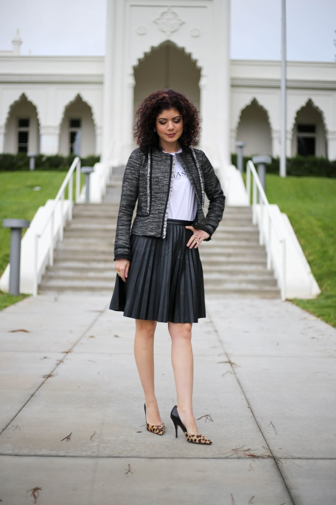 Fashion blogger polished whimsy styling a graphic tee for work with a leather pleated skirt, tweed jacket and leopard print pumps