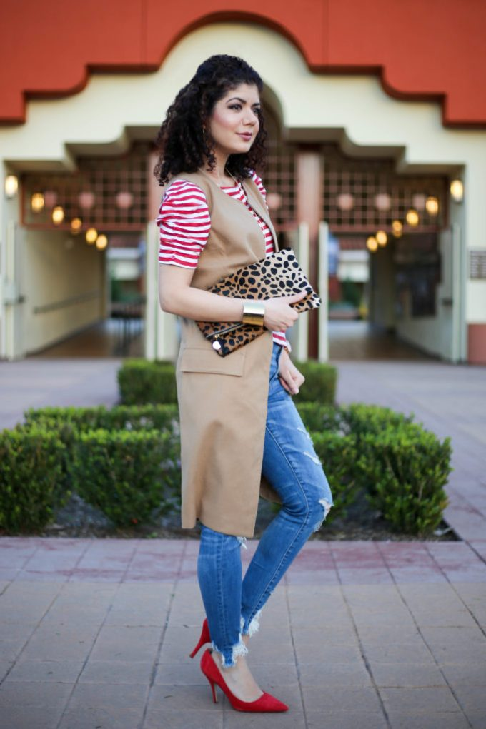 Everyday style blogger polished whimsy wearing distressed high waisted jeans, camel long vest, red stripes tee shirt, red pumps and leopard print clutch for a spring ready work outfit.