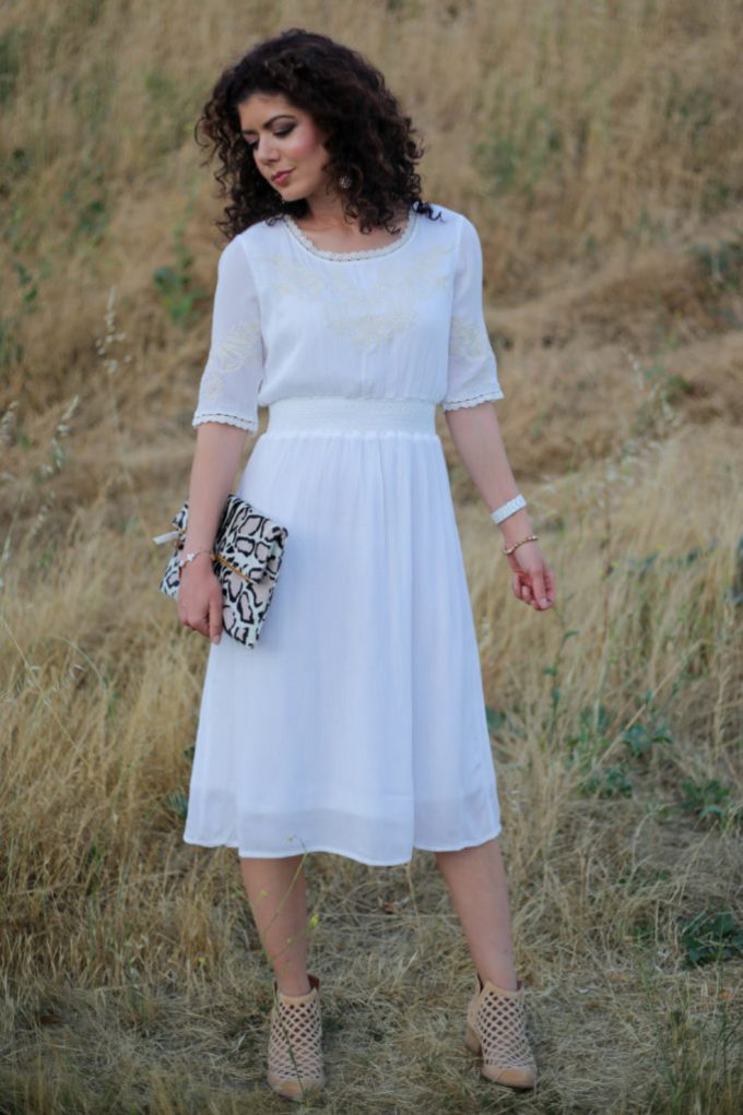 Boho white dress with polished accessories inclucing clare v snow leopard clutch