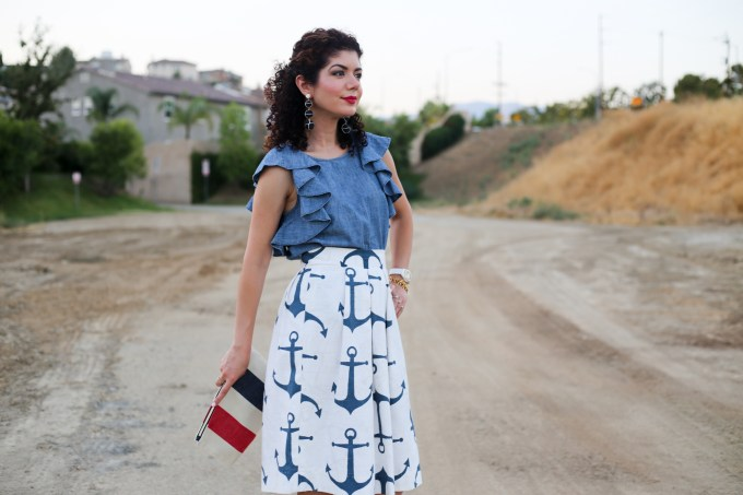 Pattern mixing outfit featuring anchor print skirt and striped clutch