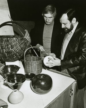 """Olaf Harringer (left), exhibits manager at the Museum of Science and Industry in Chicago, and Theodor J. Swigon, assistant exhibits manager, inspect pottery, glassware, textiles, and other pieces from the """"Artist-Craftsmen of the Federal Republic of Germany"""" exhibit."""