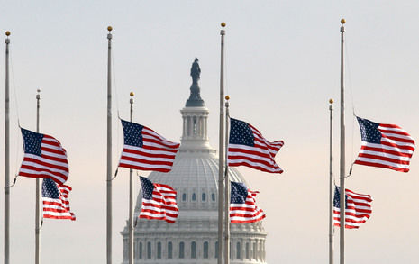 Flags at the Washington Monument fly at half staff honoring Sen. Arlen Specter of Pennsylvania, with the dome of the U.S. Capitol in the background.