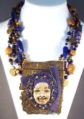 polymer clay bead and face necklace with cobalt glass and brass
