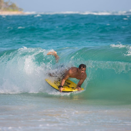 Man body boarding in surf of the shores of Laie Hawaii