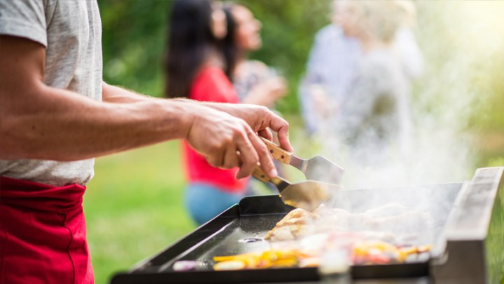 Outdoor cooking on outdoor grill or kitchen with tongs and apron