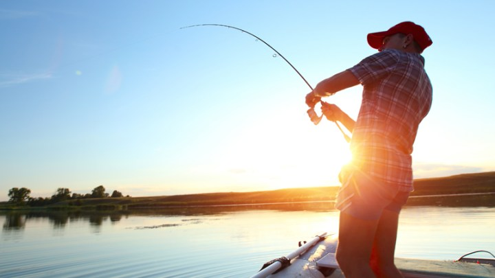 Man on fishing boat on a lake at sunset fishing as an outdoor hobby