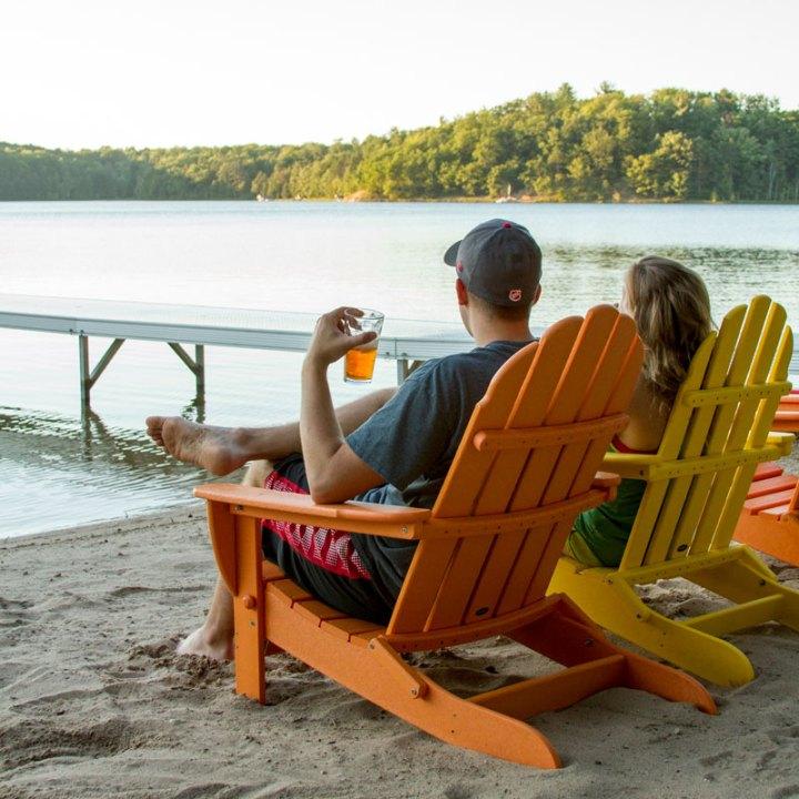 couple watching the sunset on polywood adirondack chairs