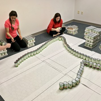 "The Atlanta Canstruction team practices the ""Can Goddess"" build."