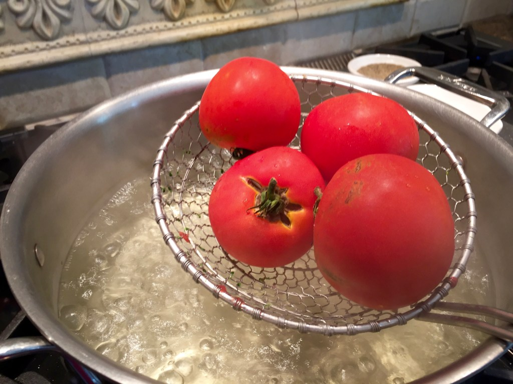 Freezer pasta sauce: How to peel a tomato - next, submerge them in boiling water for a few seconds.