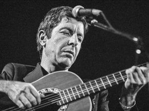 Leonard Cohen joven interpretando con su guitarra