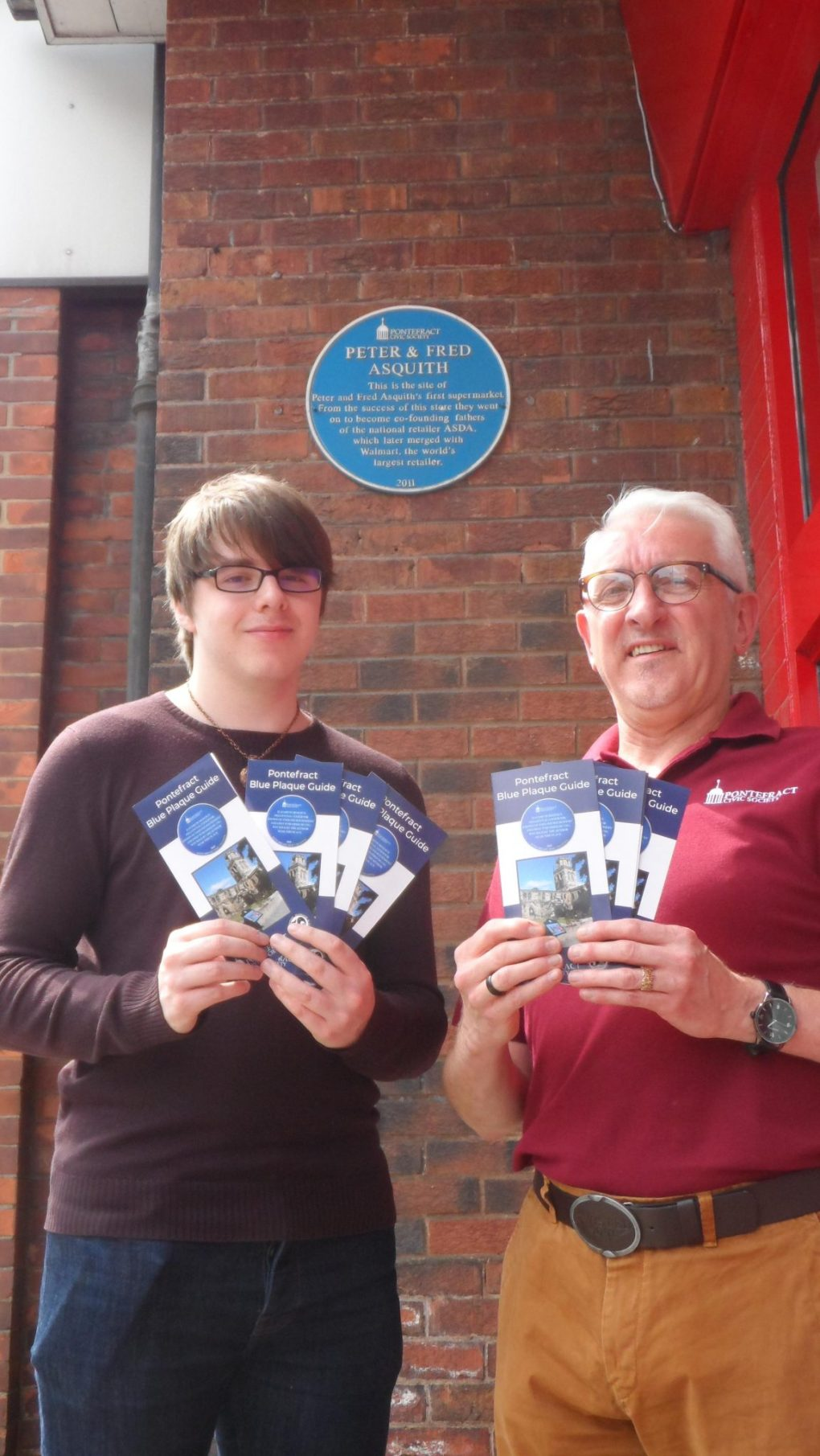 Chairman Paul Cartwright and volunteer Jaydn Edwards standing together, holding the new Blue Plaque Guides by the Peter and Fred Asquith plaque.