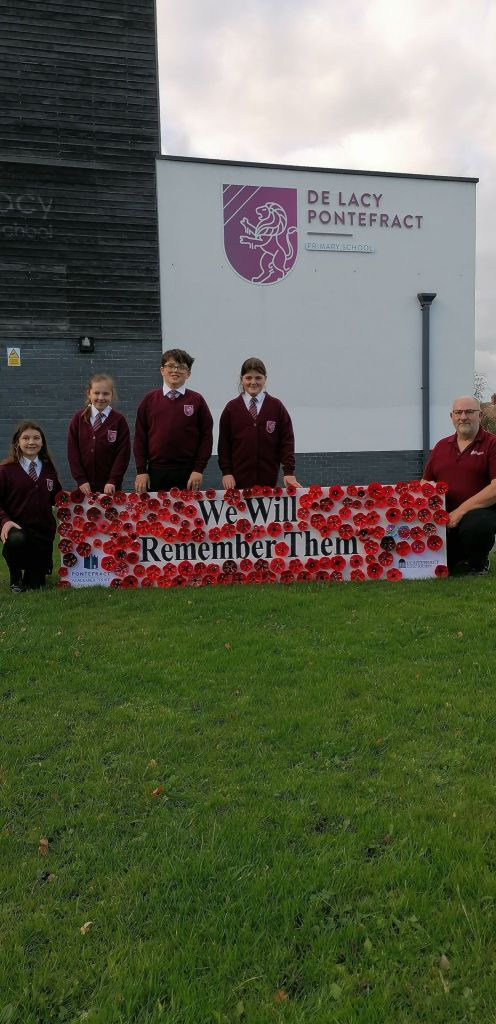 Vice-Chair Phil stands by a remembrance display with De Lacey Academy pupils.