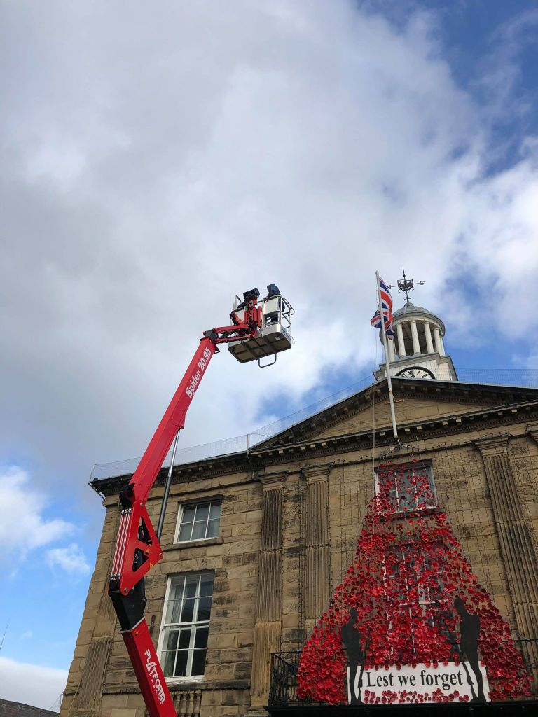 Poppies being installed on the Town Hall via TSS Lift.
