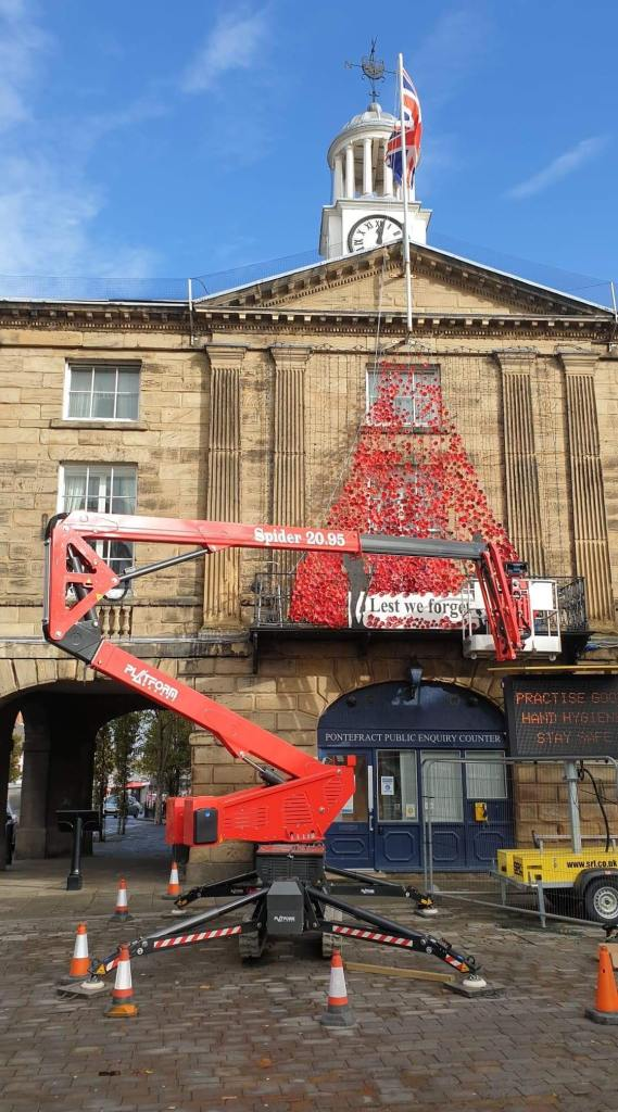 Poppies being installed on the Town Hall.